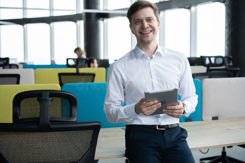 Hombre joven feliz que sonr?e en la c?mara con una tableta en su mano imagen de archivo libre de regalías