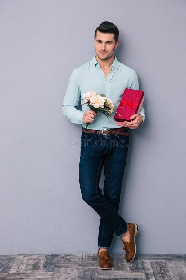 Hombre joven feliz que sostiene la caja y las flores de regalo fotografía de archivo