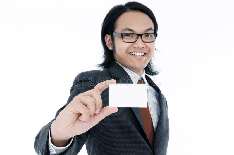 Hombre joven feliz que sostiene una tarjeta en blanco imagen de archivo