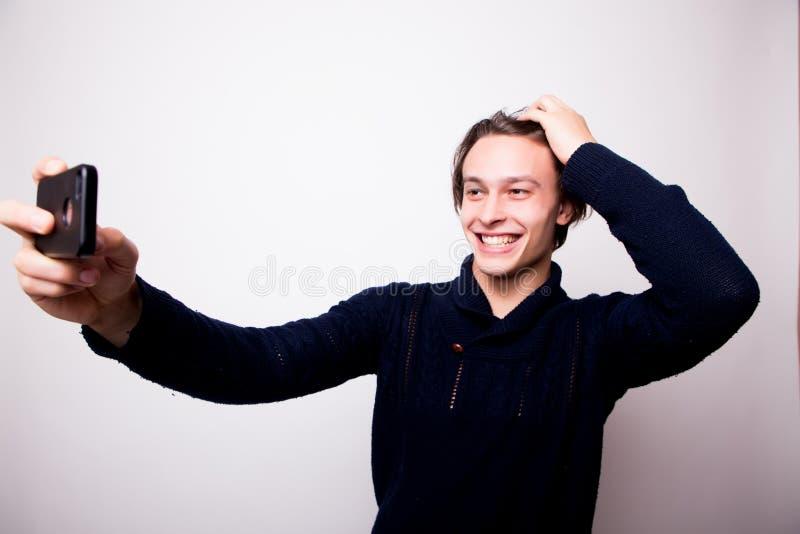 Hombre joven feliz que toma fotografía del autorretrato a través del teléfono elegante foto de archivo