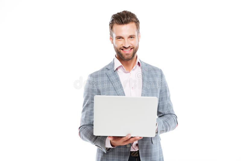 Hombre joven feliz que usa el ordenador portátil fotos de archivo libres de regalías