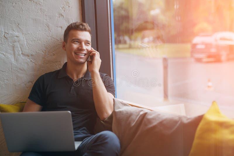 Hombre joven feliz que usa el ordenador portátil y el teléfono móvil en el sofá foto de archivo