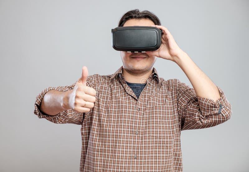 Hombre joven feliz que usa las auriculares de la realidad virtual imágenes de archivo libres de regalías