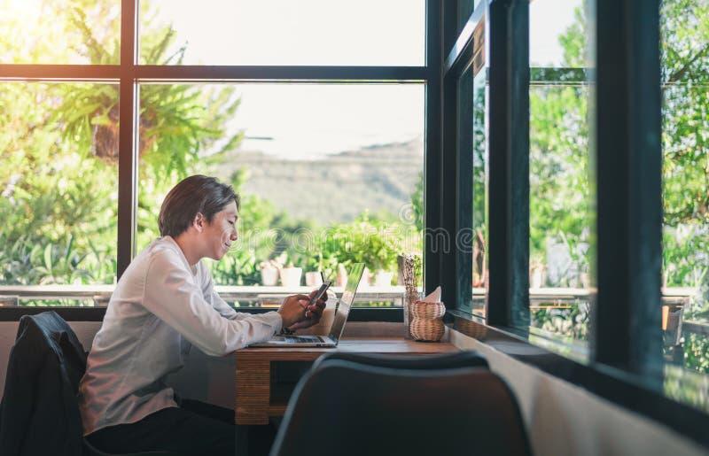 Hombre joven feliz, vidrios que llevan y sonrisa, como él trabaja en su ordenador portátil para conseguir todo su negocio hecho t imagen de archivo