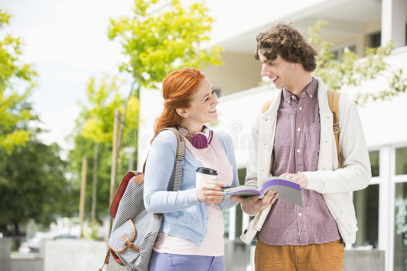 Hombre joven feliz y mujer que estudian junto en el campus de la universidad imagen de archivo libre de regalías