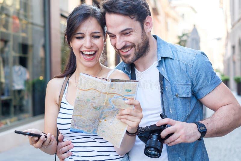 Hombre joven feliz y mujer sonriente que caminan alrededor de la calle vieja de la ciudad foto de archivo libre de regalías