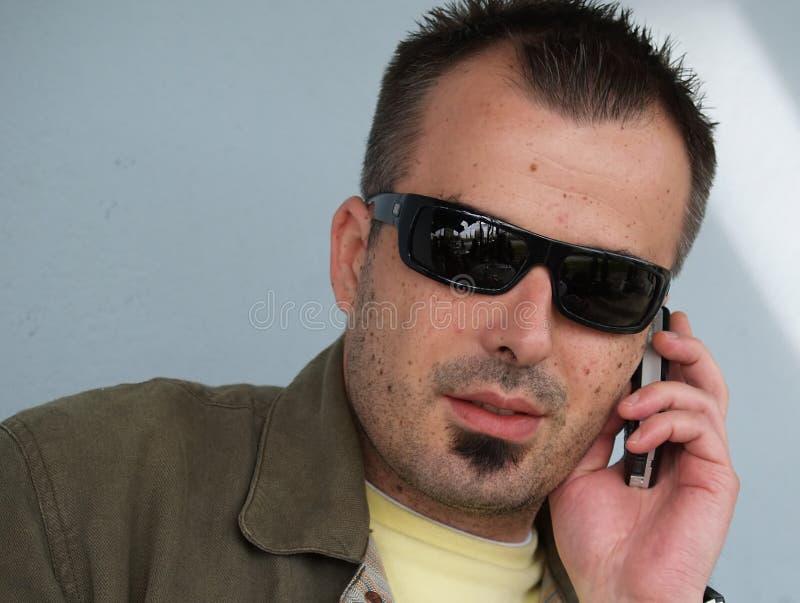 Hombre joven fresco que hace una llamada de teléfono fotografía de archivo libre de regalías