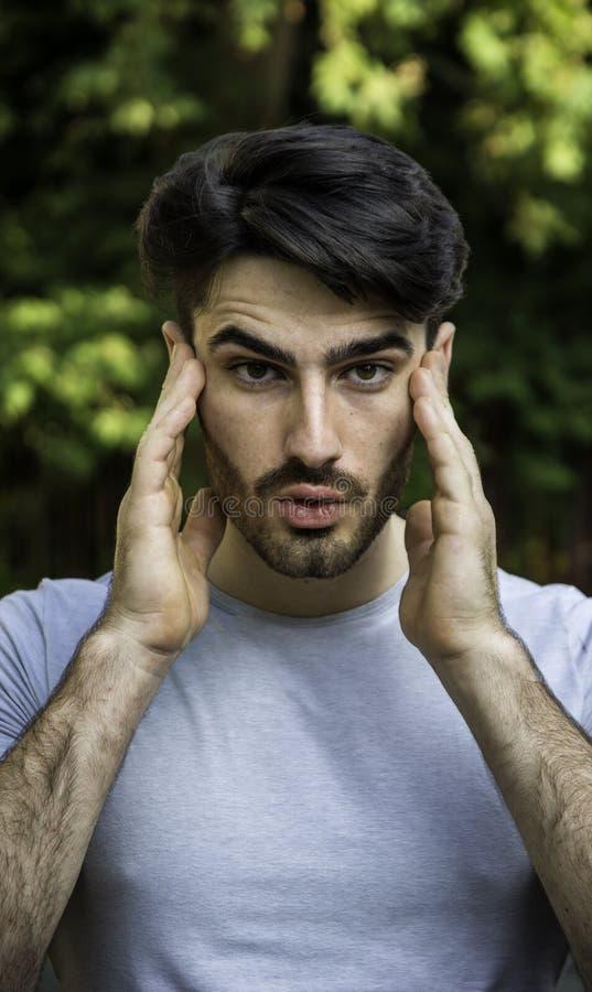 Hombre joven frustrado con dolor de cabeza imagen de archivo