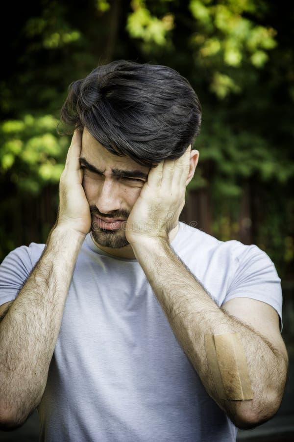 Hombre joven frustrado con dolor de cabeza fotografía de archivo libre de regalías