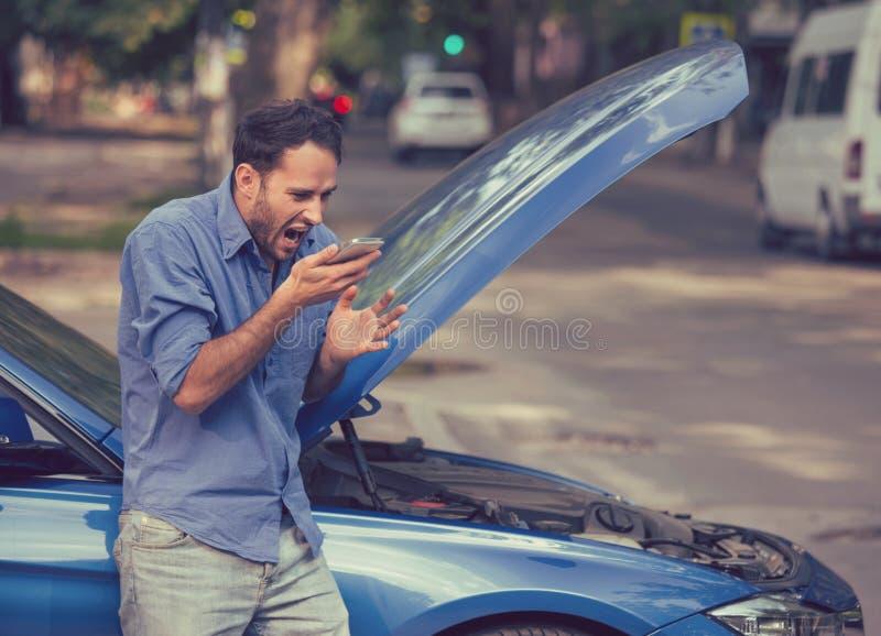 Hombre joven frustrado que llama ayuda del borde de la carretera después de analizar imagen de archivo libre de regalías