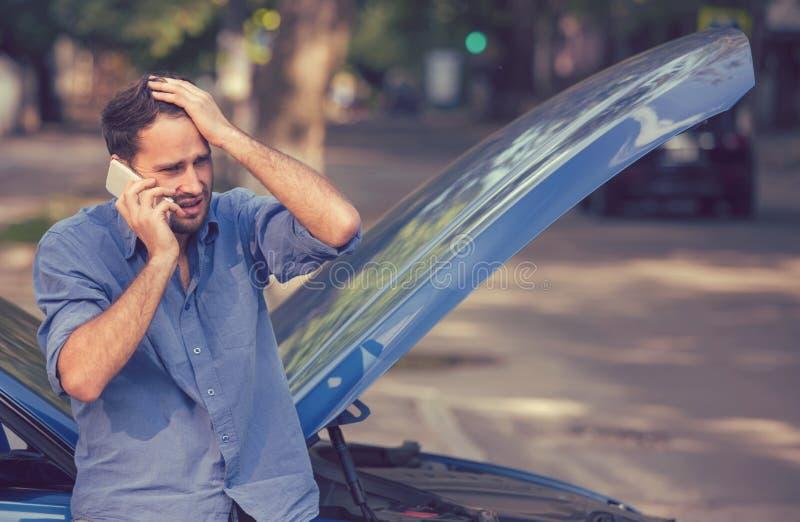 Hombre joven frustrado que llama ayuda del borde de la carretera después de analizar foto de archivo libre de regalías