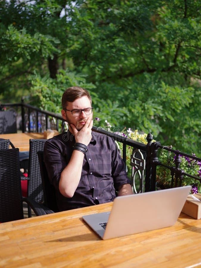Hombre joven grande que trabaja en el ordenador portátil mientras que se sienta al aire libre Concepto del asunto imágenes de archivo libres de regalías