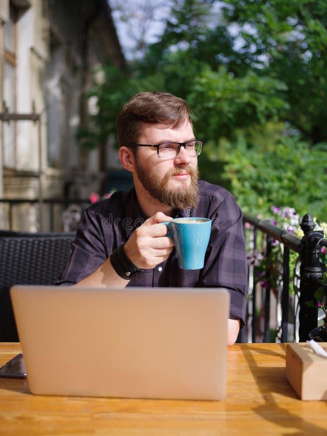 Hombre joven grande que trabaja en el ordenador portátil mientras que se sienta al aire libre Concepto del asunto foto de archivo libre de regalías