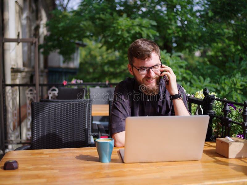 Hombre joven grande que trabaja en el ordenador portátil mientras que se sienta al aire libre Concepto del asunto fotos de archivo