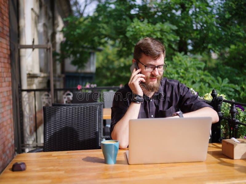 Hombre joven grande que trabaja en el ordenador portátil mientras que se sienta al aire libre Concepto del asunto fotografía de archivo libre de regalías