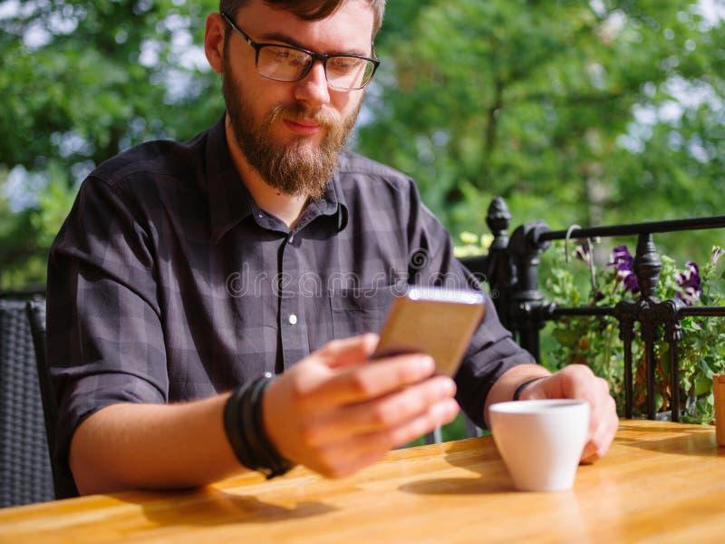 Hombre joven grande que trabaja en la tableta mientras que se sienta al aire libre Concepto del asunto imágenes de archivo libres de regalías