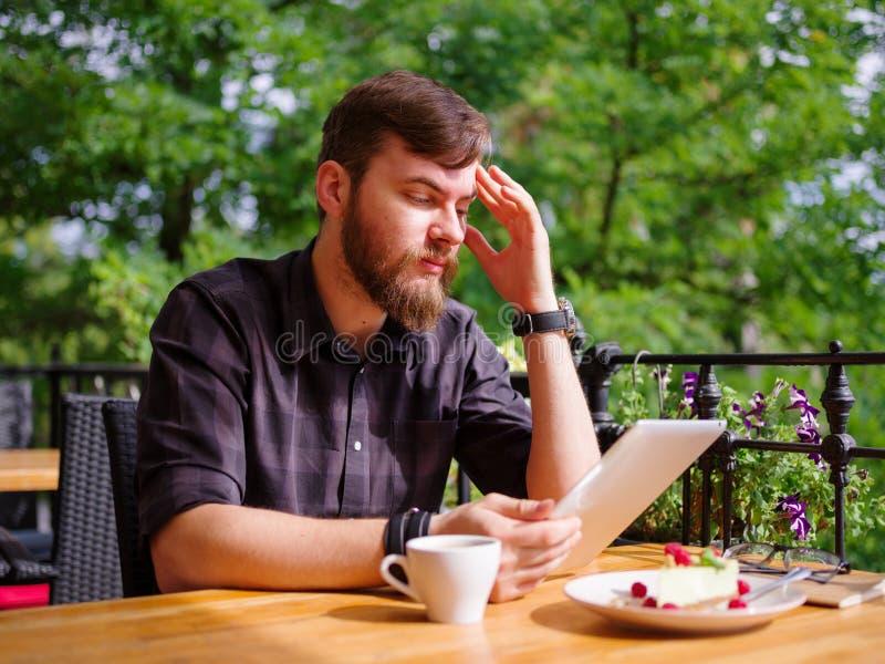 Hombre joven grande que trabaja en la tableta mientras que se sienta al aire libre Concepto del asunto fotos de archivo