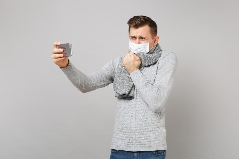 Hombre joven gritador en el suéter gris, el hablar estéril de la mascarilla de la bufanda, haciendo la llamada video con el teléf fotos de archivo libres de regalías