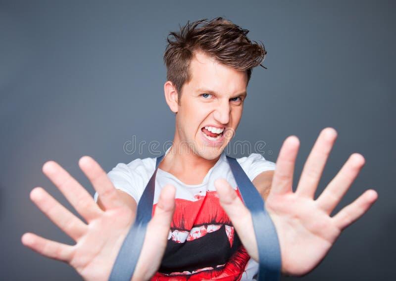 hombre joven hermoso agresivo con las paréntesis en gre foto de archivo