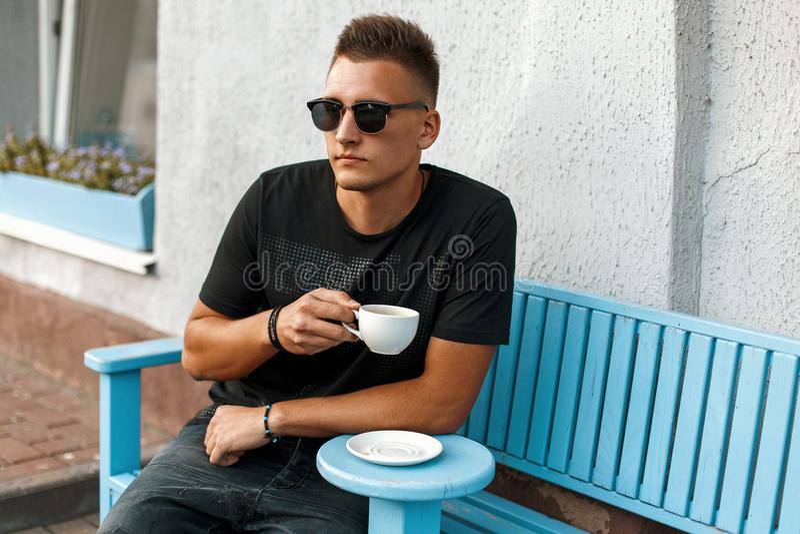Hombre joven hermoso con el café que se sienta en un banco foto de archivo