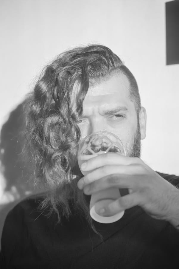 Hombre joven hermoso con el pelo rizado largo y una barba ¡Morenita brutal del hombre en una camiseta negra y con un corte de pel foto de archivo