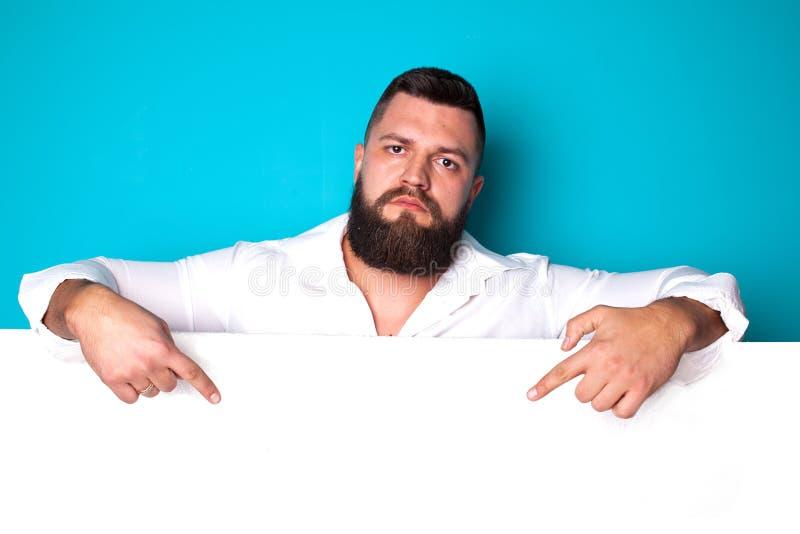 Hombre joven hermoso con la barba larga y bigote en cara con señalar el finger en fondo azul en el estudio, espacio de la copia imagen de archivo libre de regalías