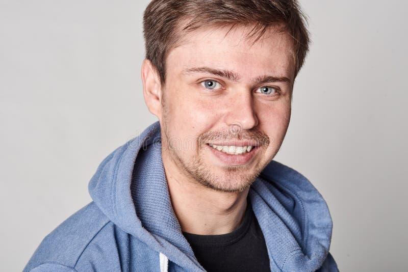 Hombre joven hermoso con la barba ligera en sudadera con capucha azul, en el CCB gris imagen de archivo