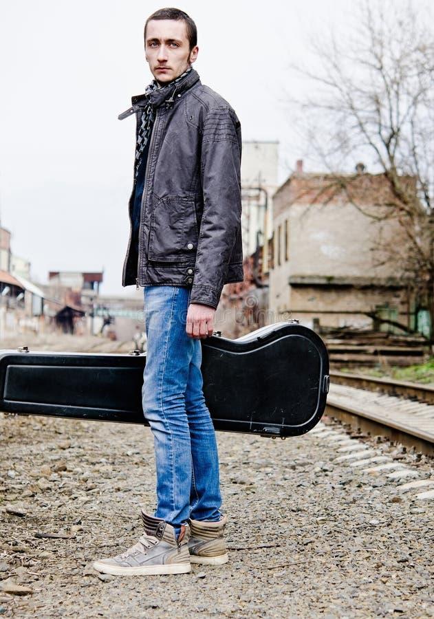Hombre joven hermoso con la caja de la guitarra a disposición entre ruinas industriales fotos de archivo libres de regalías