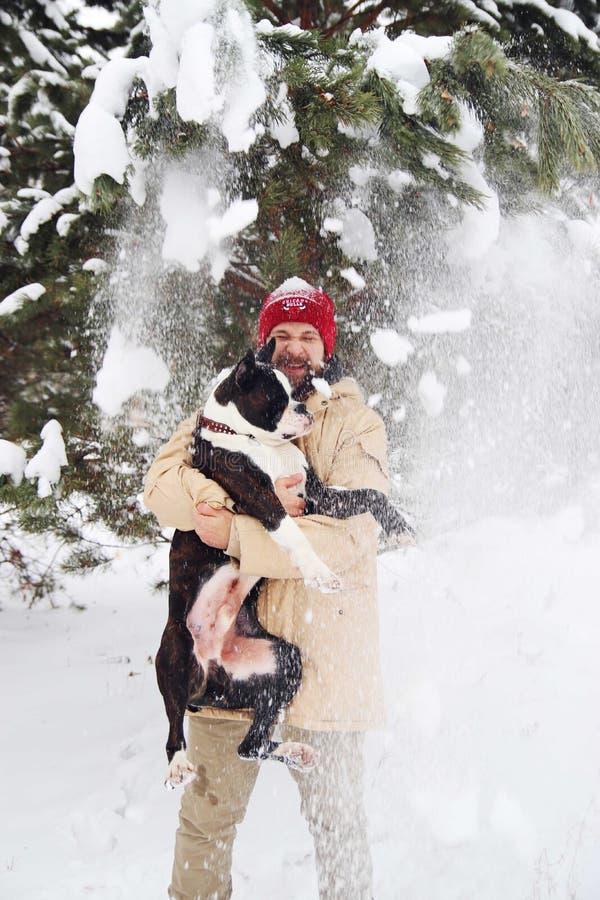 Hombre joven hermoso con su perro del boxeador al aire libre imagen de archivo
