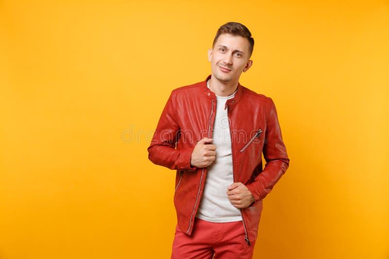 Hombre joven hermoso confiado de la voga del retrato 25-30 años en la chaqueta de cuero roja, soporte de la camiseta aislado en t foto de archivo libre de regalías