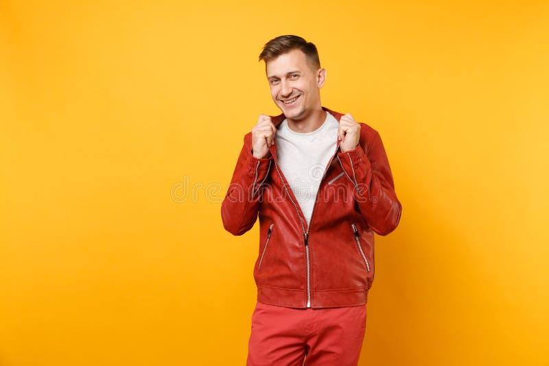 Hombre joven hermoso confiado de la voga del retrato 25-30 años en la chaqueta de cuero roja, soporte de la camiseta aislado en t imagen de archivo