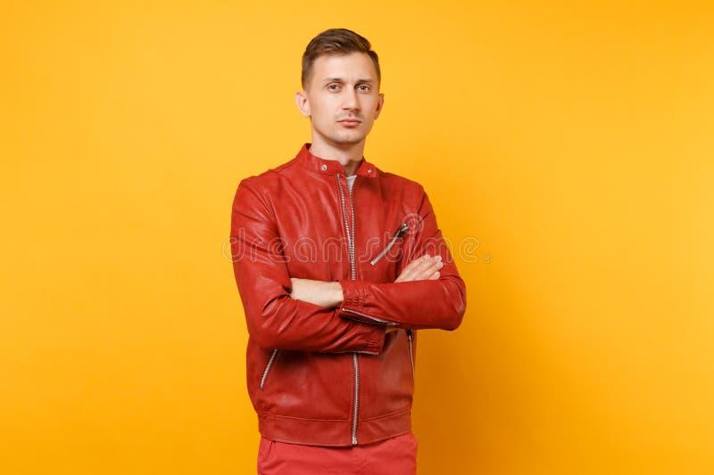 Hombre joven hermoso confiado de la voga del retrato 25-30 años en la chaqueta de cuero roja, soporte de la camiseta aislado en t foto de archivo