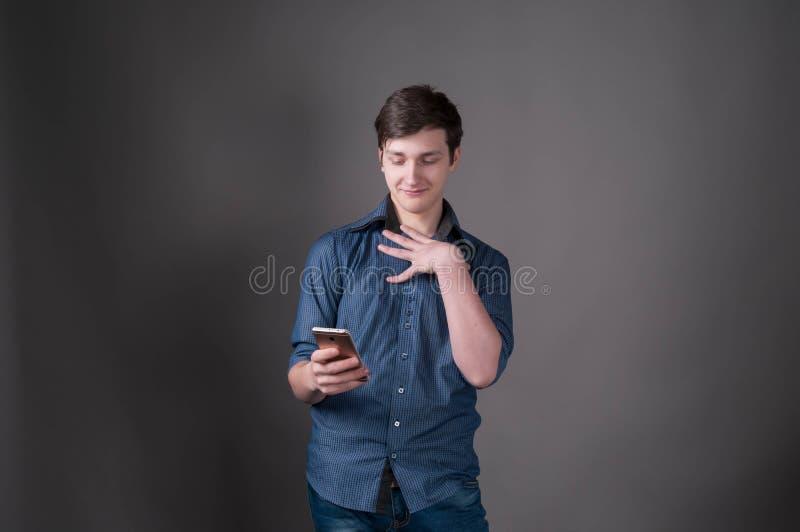 Hombre joven hermoso confuso en camisa azul que sonríe y que mira smartphone en fondo gris foto de archivo