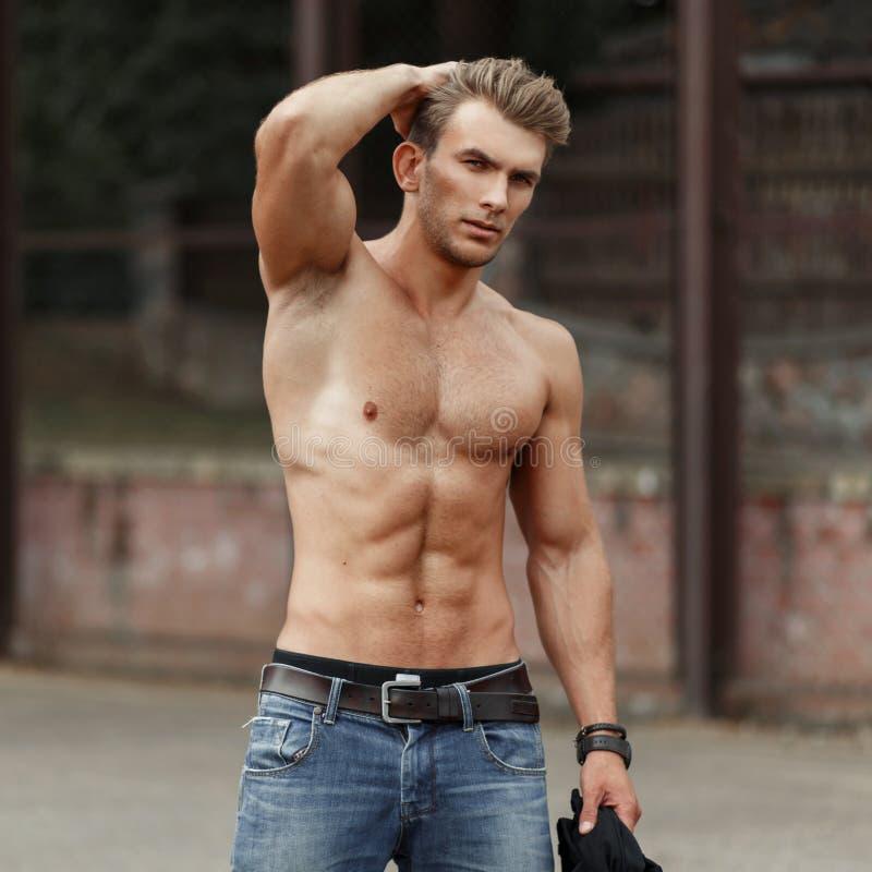 Hombre joven hermoso elegante con un cuerpo sano hermoso con fotografía de archivo