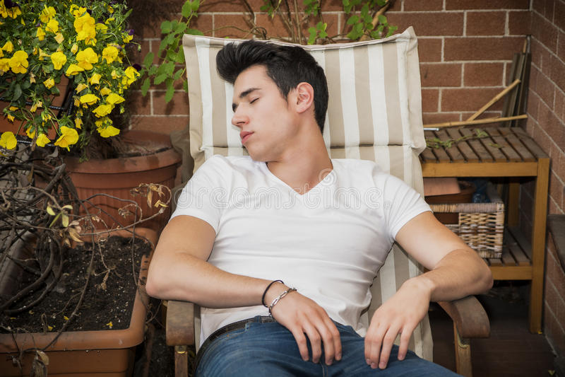 Hombre joven hermoso en balcón que duerme en silla fotos de archivo