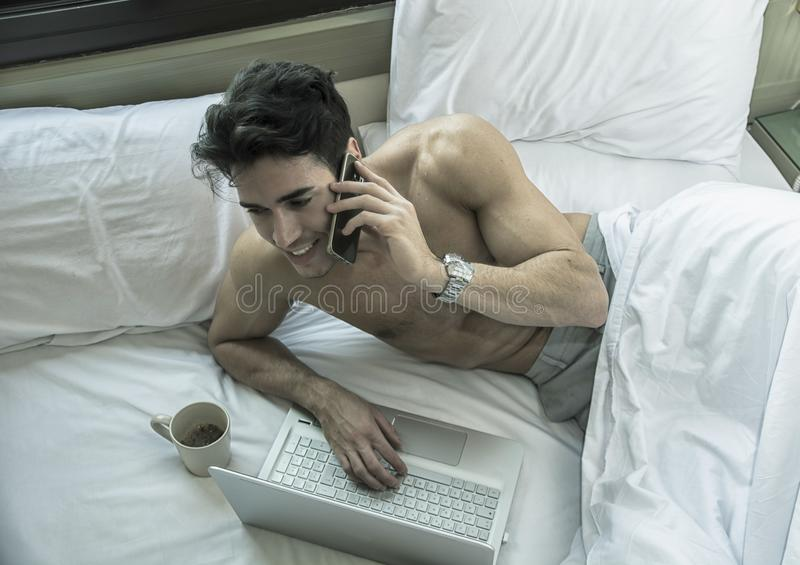 Hombre joven hermoso en cama que invita al teléfono celular imagen de archivo