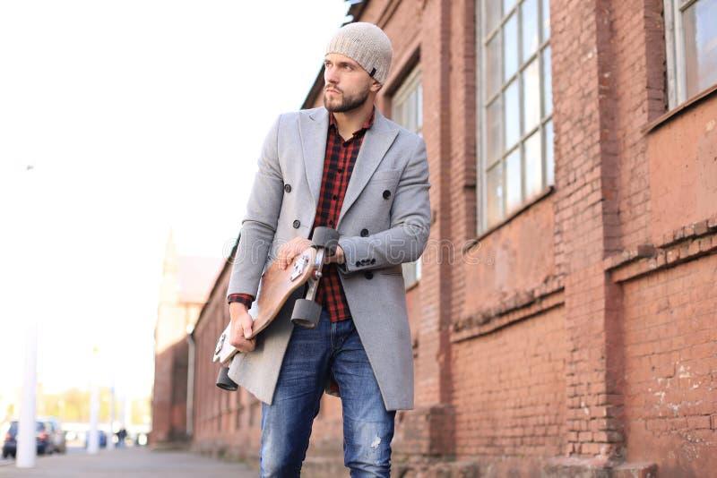 Hombre joven hermoso en capa y sombrero grises que camina en la calle, usando longboard foto de archivo libre de regalías