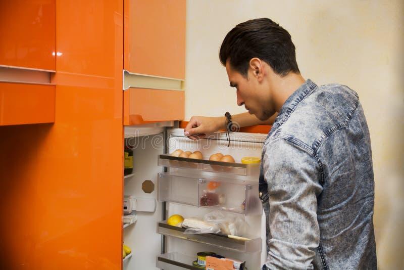 Hombre joven hermoso en casa que mira el refrigerador interior fotografía de archivo libre de regalías