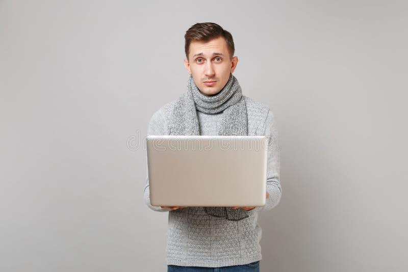Hombre joven hermoso en el suéter gris, funcionamiento de la bufanda en el ordenador de la PC del ordenador portátil en fondo gri foto de archivo libre de regalías