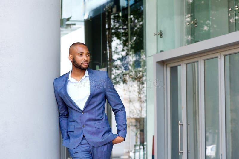 Hombre joven hermoso en el traje de negocios que se inclina contra la pared al aire libre imágenes de archivo libres de regalías