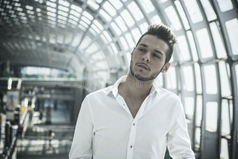 Hombre joven hermoso en la estación o el aeropuerto de tren fotos de archivo