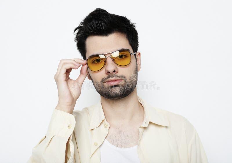 Hombre joven hermoso en ropa de sport elegante con las gafas de sol fotografía de archivo libre de regalías
