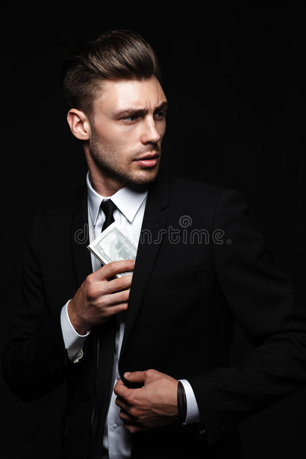 Hombre joven hermoso en traje en fondo oscuro con foto de archivo libre de regalías