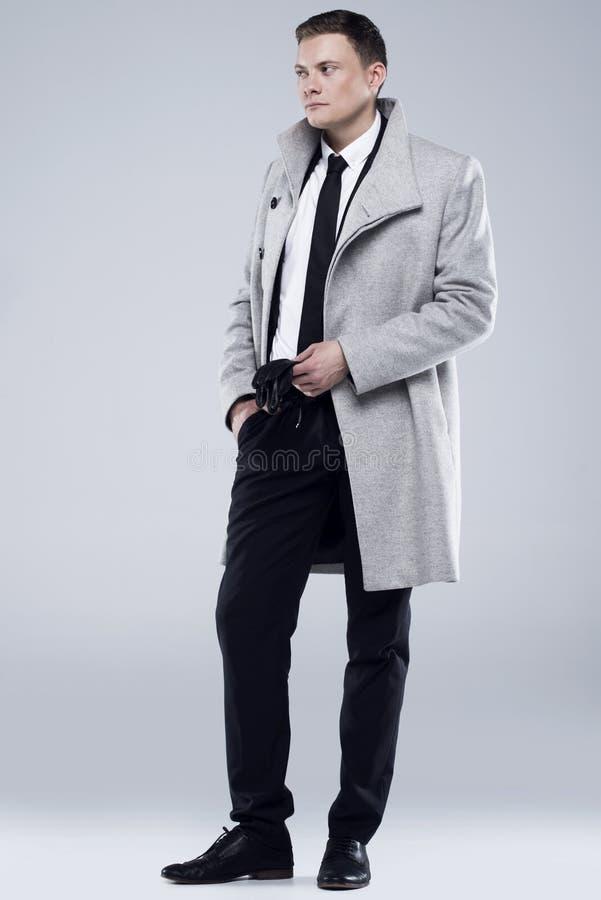 Hombre joven hermoso en una capa gris y un traje negro fotos de archivo libres de regalías