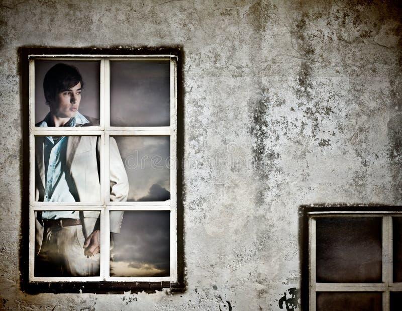 Hombre joven hermoso en una ventana fotografía de archivo