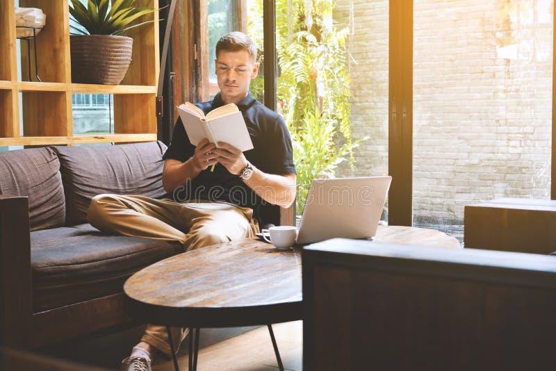 Hombre joven hermoso feliz que lee un libro fotos de archivo libres de regalías
