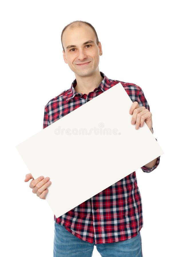 Hombre joven hermoso feliz que sostiene la tarjeta blanca en blanco imagen de archivo libre de regalías