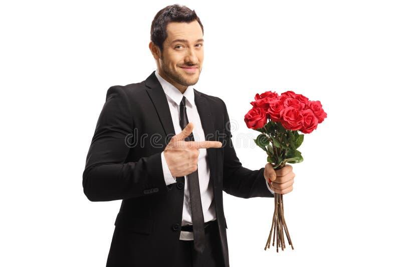 Hombre joven hermoso fresco que sostiene un manojo de rosas rojas y que señala en ellas imágenes de archivo libres de regalías