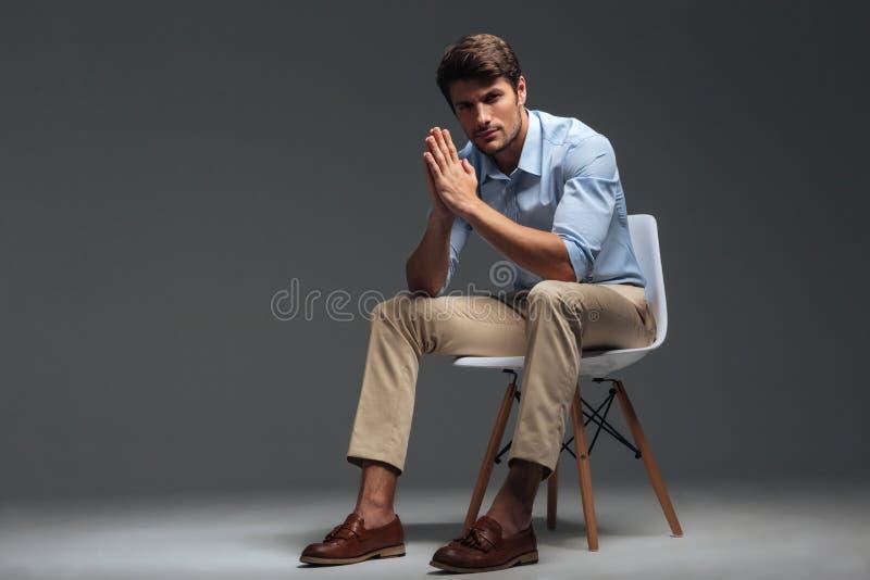 Hombre joven hermoso pensativo que se sienta en silla y que mira la cámara imágenes de archivo libres de regalías