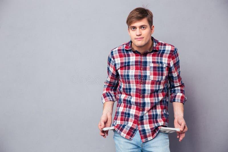 Hombre joven hermoso pobre en la camisa a cuadros que muestra los bolsillos vacíos foto de archivo